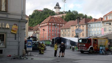 Firemen and police stand next to a damaged bicycle at the site where a man drove his van into a crowd at the main square in Graz, southern Austria, Saturday, June 20, 2015. According to officials three people were killed in the incident and 34 injured.