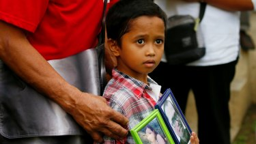 Adrian Perigrino holds portraits of his parents, both victims of extra-judicial killing, in suburban Paranaque city south of Manila in March.