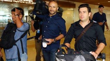 Reporter Linton Besser, right, and camera operator Louie Eroglu prepare to leave at Kuching International Airport.
