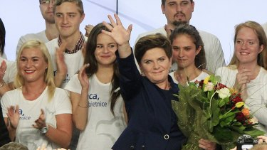 The candidate for prime minister, Beata Szydlo, waves after her Eurosceptic party defeats the pro-EU Civic Platform.