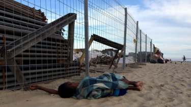 A boy sleeps next to ongoing construction of the Olympic Beach Volleyball Arena on Copacabana Beach on on Monday.