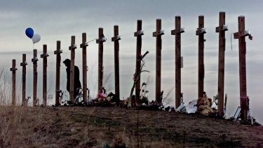 A woman stands among 15 crosses on a hill above Columbine High School in remembrance of the 15 people who died during a school shooting on April 20, 1999.