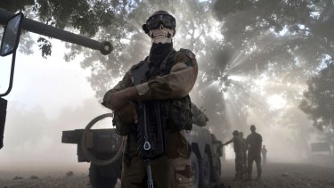 A French soldier wearing a skeleton mask stands next to a tank in a street in Niono, Mali, in 2013.