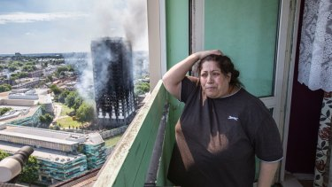 Local resident Georgina stands distraught on her balcony after a fire engulfed the 24-storey Grenfell Tower.
