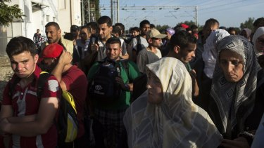 Refugees wait to be let through a police line at the Tovarnik train station in Croatia on Thursday in the hope of boarding buses headed to Zagreb.