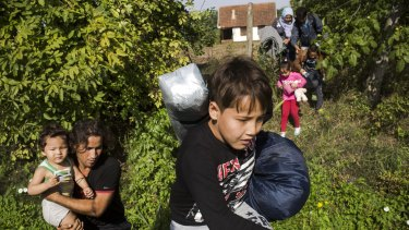 A family of refugees in Horgos, Serbia,  rush towards the border with Hungary after hearing a rumour (which turned out to be false) that the Hungarian authorities had opened the crossing.