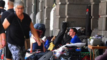 A man sits at the homeless camp outside Flinders Street Station.