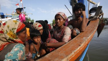 Rescued migrants sit on an Acehnese fishing boat upon arrival in Indonesia.