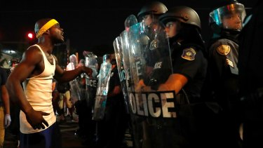 A man yells at police in riot gear just before a crowd turned violent in St Louis.
