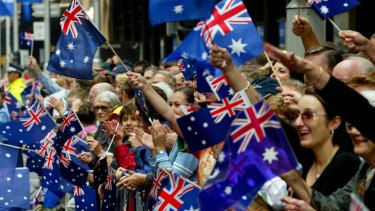 The flag-waving crowd on George Street, Sydney, as the Anzac Day march passes by.