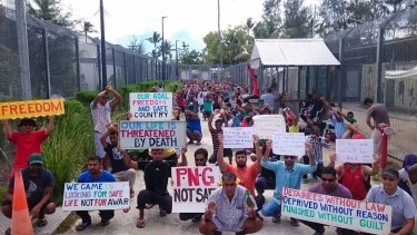 In this undated photo released by Refugee Action Coalition, refugees and asylum seekers hold up banners during a protest at the Manus Island immigration detention centre.