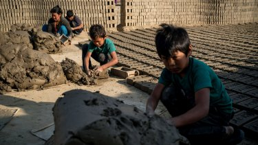Phursang Tamang, 10, (centre) works with his brother and parents at a brick factory in Bhaktapur. The Tamang family's house was damaged beyond repair.