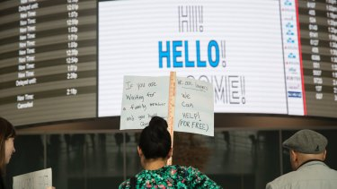 Volunteer lawyers stand with signs to greet arriving passengers in John F. Kennedy International Airport in New York,.