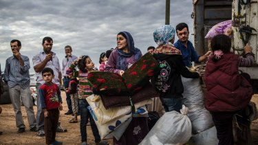 A family hurries to board a truck bound for shelter for Syrian Kurdish refugees in Yumurtalik, Turkey, in September 2014. Turkey is refuge to more Syrian refugees than any other country.