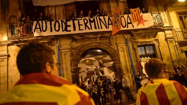 Pro-independence supporters wrapped in ''esteleda'' or Catalan flags stand in front a balcony while people protest with a banner reading ''self determination''.