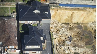 The earth below the pit-side townhouses is now unstable and the buildings could fall into the hole.