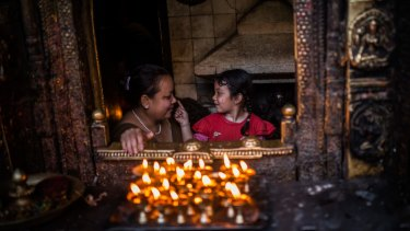 A young girl caresses her mother's nose in a temple in Kathmandu, Nepal, on Monday.