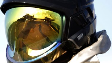 The deck of the French Navy aircraft carrier Charles de Gaulle is reflected in the helmet of a crew member.