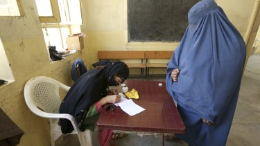 An Afghan woman, right, waits to receive a ballot paper at a polling station in Jalalabad  in June 2014.