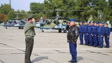 Russian military pilots, right, report upon arrival at an airbase at an undisclosed location in Belarus.