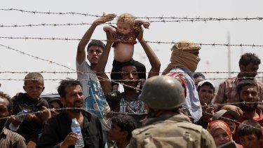 Syrian refugees on the Syrian side of the border crossing at Akcakale on Monday.