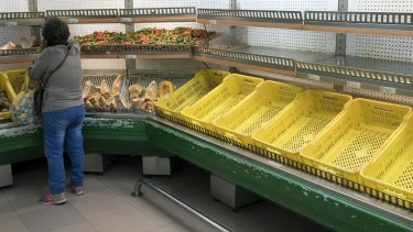 A customer reaches for pumpkin slices for sale near empty shelves at a grocery store in Caracas last week.