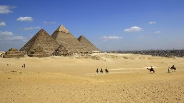 Gunmen on a speeding motorcycle opened fire outside the plateau of the famed Giza Pyramids on the outskirts of Cairo early on Wednesday, killing two policemen.