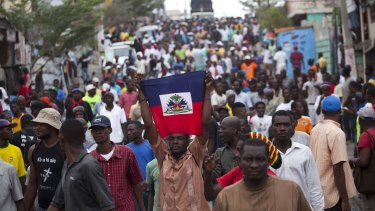 Anti-government protesters hold up the Haitian flag. Annual Carnival celebrations have been sidelined by the political demonstrations.