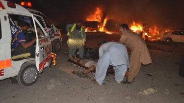 Pakistani volunteers help an injured person awaiting an ambulance to take them to a hospital in Quetta, Pakistan, on Saturday.