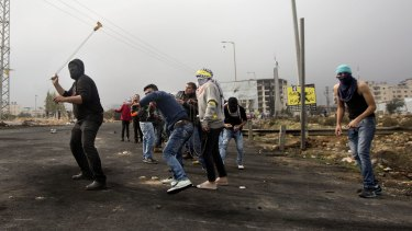 Palestinians protesters throw stones at Israeli troops during clashes in the West Bank city of Ramallah on Monday.