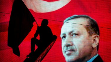 A supporter of Turkish President Recep Tayyip Erdogan waves a flag against an electronic billboard during a rally in Kizilay Square in July.
