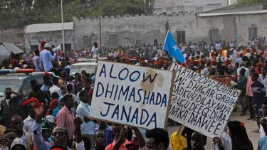 """Protesters march on Wednesday with placards reading """"Out al- Shabab"""", left, and """"Oh God, have mercy on the dead"""" near the scene of Saturday's massive truck bombing in Mogadishu."""
