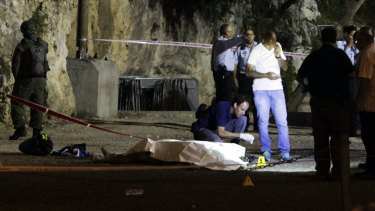 Israeli police stand around a body of a Palestinian after the attack in Jerusalem's occupied Old City on Friday.