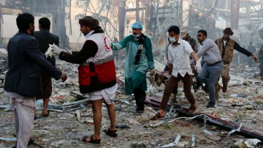 Medics carry the body of a victim of a Saudi-led coalition airstrike in Sanaa, Yemen.