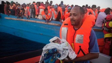 A man carries his five-day-old son onto an Italian vessel after been rescued from a crowded wooden boat fleeing Libya.