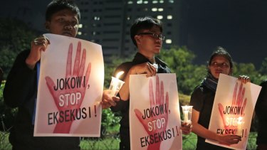 """Activists hold posters which read """"Jokowi, stop the executions!"""" during a candle light vigil outside the presidential palace in Jakarta, on Thursday."""