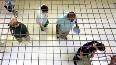 Prisoners wait to collect food in C wing at Wandsworth Prison.