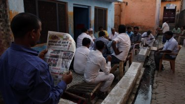 A relative of Mohammad Akhlaq reads a newspaper carrying news of Akhlaq's killing.