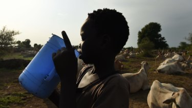 A boy drinks fresh milk at the cattle camps that have popped up on the outskirts of Bentiu in South Sudan.
