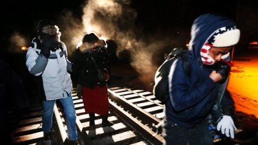 Eight migrants from Somalia cross into Canada illegally from the US on February 26, walking down a train track into the town of Emerson, Manitoba.