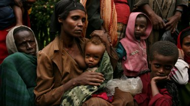 Bussa Shalamo, second from left with her two children wait in a queue with 2000 strong crowd at a MSF Belgium outreach clinic in southern Ethiopia.