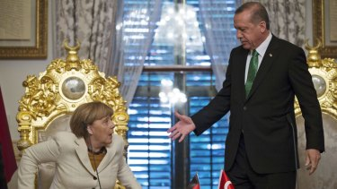 Mr Erdogan offers his hand to German Chancellor Angela Merkel following a  meeting in Istanbul on October 18.