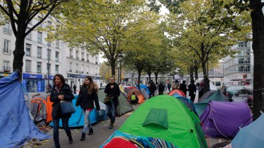 People walk between tents in a makeshift camp, in Paris, on Friday.