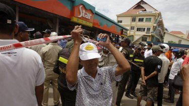 People stand outside a petrol station convenience store where Kem Ley, a political analyst was killed.