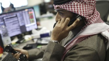 An employee speaks on the phone at the Alawwal Bank as financial data is displayed on computer screens on the bank's trading floor in Riyadh, Saudi Arabia where the central bank is said to have been crippled by malware.