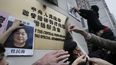Protesters with photos of missing booksellers during a protest outside the Liaison of the Central People's Government in Hong Kong.