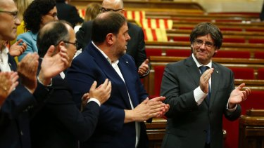 Catalonia regional President Carles Puigdemont, right, applauds with parliamentarians, after the vote to set the referendum date.