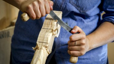 Hand carving a rocking horse's fetlock.