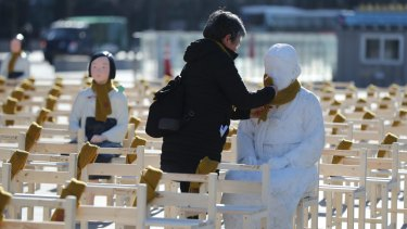 A woman puts a scarf on a statue of a comfort woman sitting in a installation of empty chairs symbolising sex slave victims in Seoul on Wednesday.