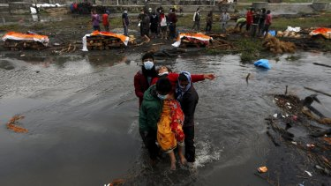 A Nepalese woman is carried after she fainted performing the last rites of her family members, who died in the earthquake.
